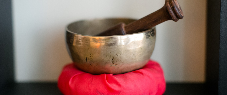 Brass Singing Bowl on Red Cushion
